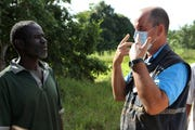 Stephen Fonseca, right, gives a community leader guidance on handling the dead April 4 in Magaru, Mozambique.