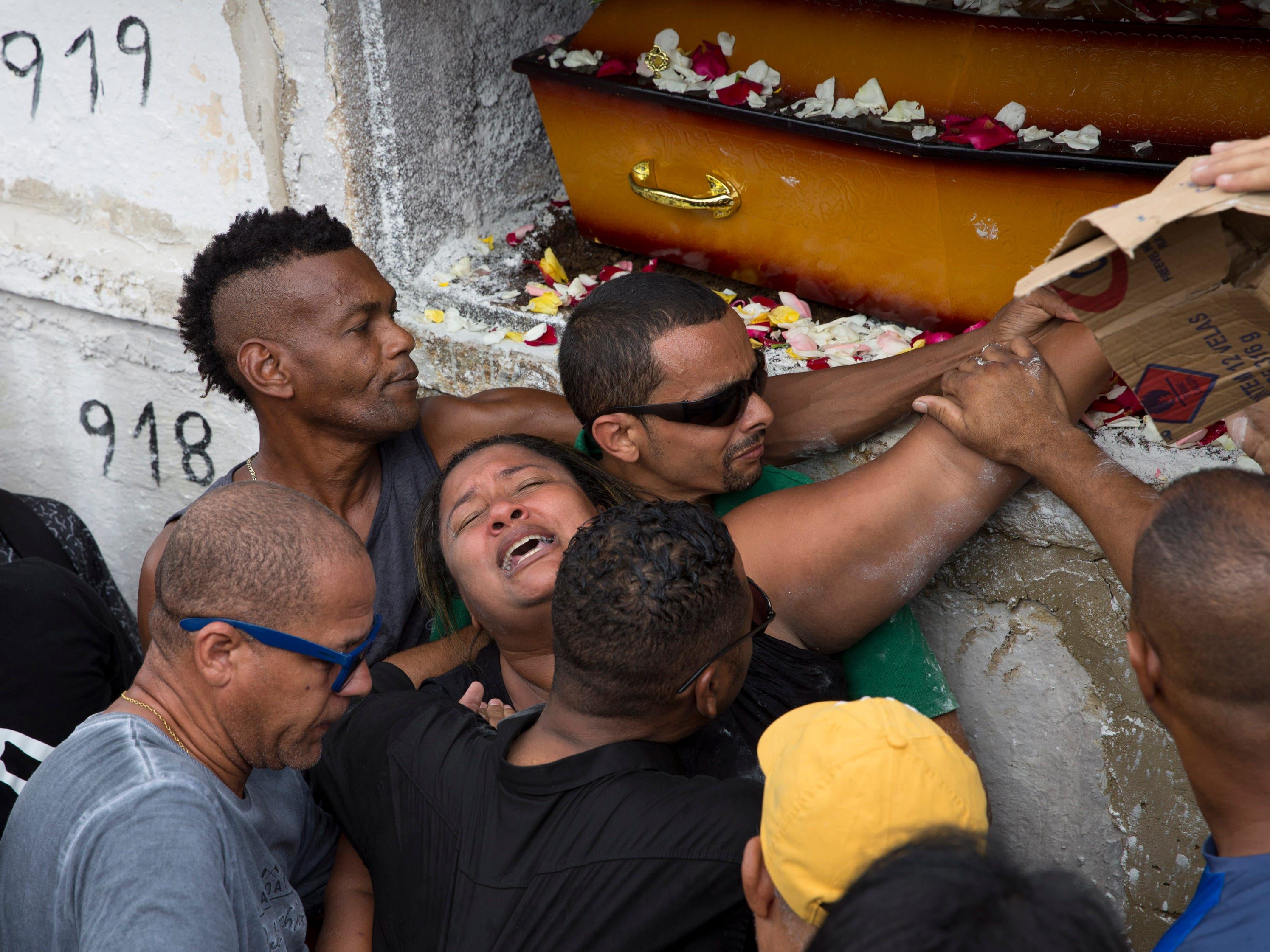 Luciana dos Santos, center, cries the burial of her husband, Evaldo dos Santos Rosa, who was killed by armed forces when they mistook his car for that of criminals, in the Ricardo de Albuquerque neighborhood of Rio de Janeiro, Brazil, Wednesday, April 10, 2019. Dos Santos Rosa was driving to a baby shower with his 7-year-old son, his wife, her stepfather and another woman when soldiers started shooting at them on Sunday.
