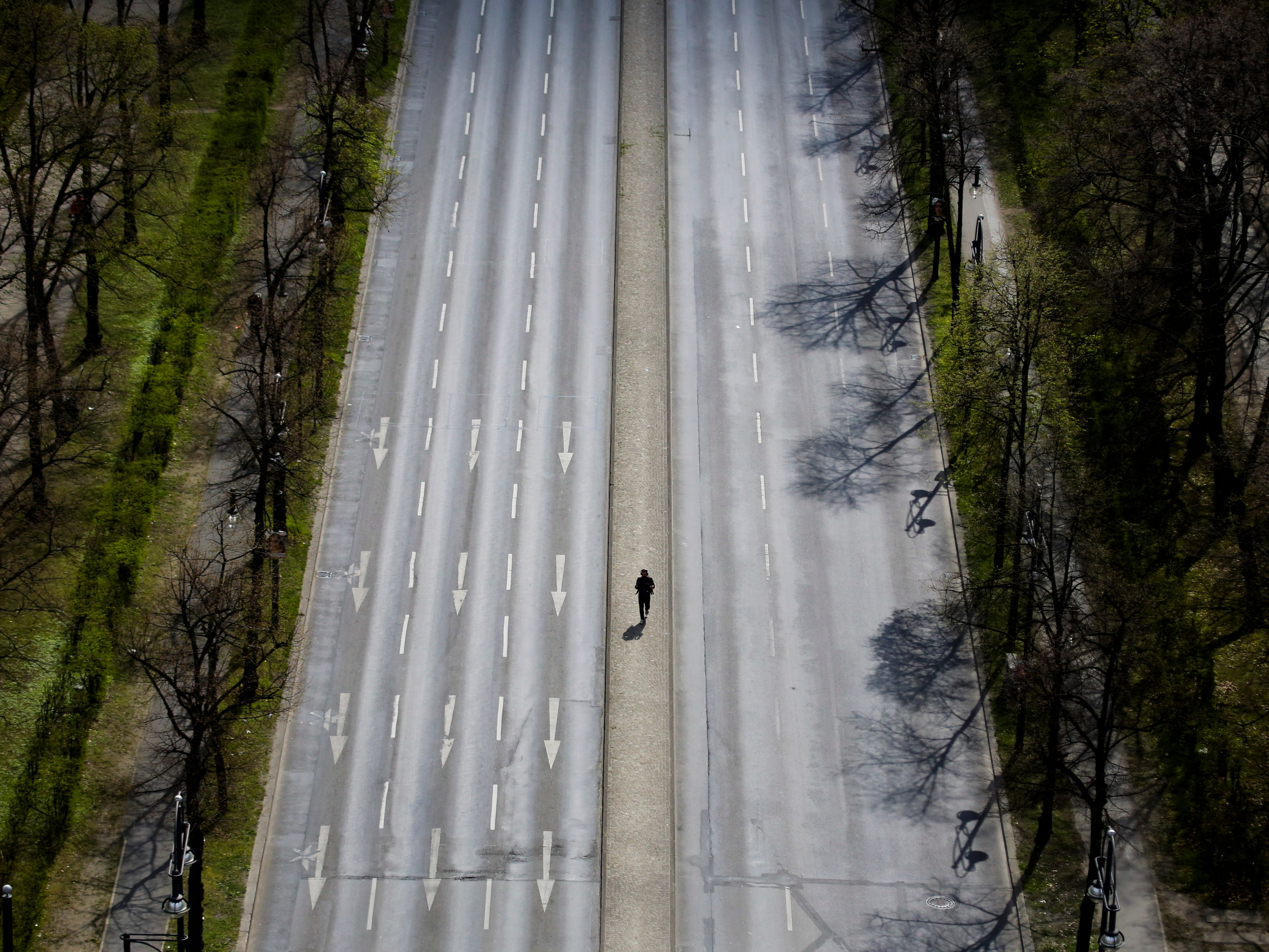 A man walks over the empty boulevard 'Hofjaegerallee' after taxi drivers blocked roads to protest the growth of app-based ride-hailing services in Berlin, Germany, Wednesday, April 10, 2019.