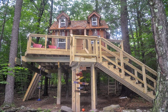"""This treehouse was built to serve as a clubhouse for kids in the Catskills of Sullivan County in upstate New York. It features an """"L-shaped"""" stairway that leads to a 10-by-14-foot house clad in reclaimed barn wood siding. With a deck that measures 19 by 22 feet, this treehouse also features a ship's ladder, rock climbing wall with built-in seating and table inside."""