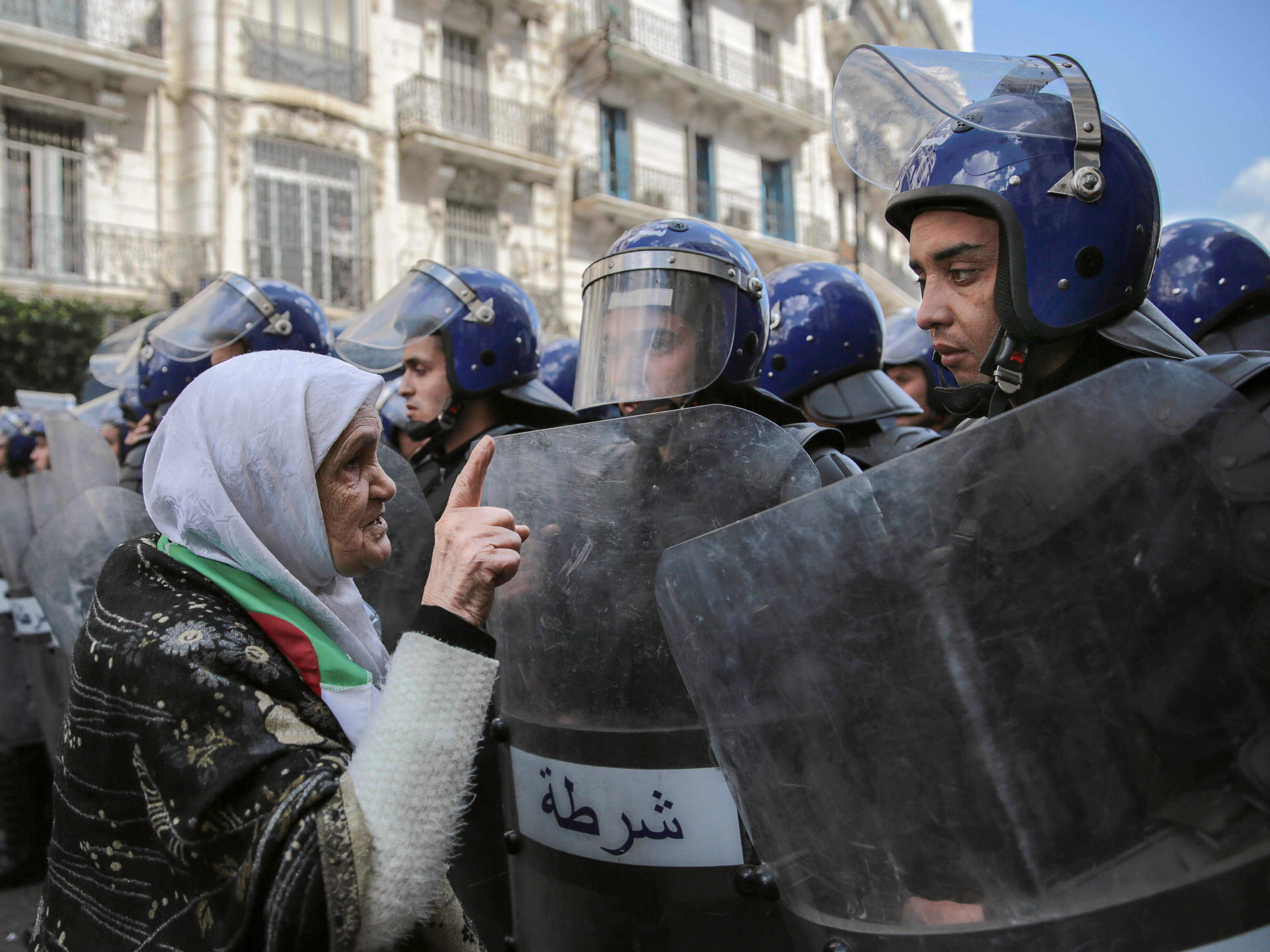 """An elderly woman confronts security forces during a demonstration in Algiers, Wednesday, April 10, 2019. The Algerian senator Abdelkader Bensalah, named to temporarily fill the office vacated by former President Abdelaziz Bouteflika, said he would act quickly to arrange an """"honest and transparent"""" election to usher in an """"Algeria of the future."""""""