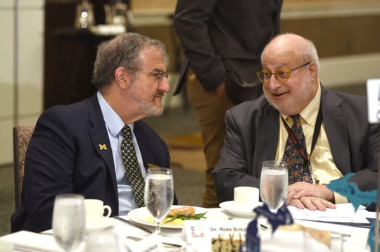 Jonathan Wolman, right, editor and publisher of The Detroit News,  speaks with Dr. Mark Schlissel, president of the University of Michigan, during a Detroit Economic Club luncheon on September 5, 2018.