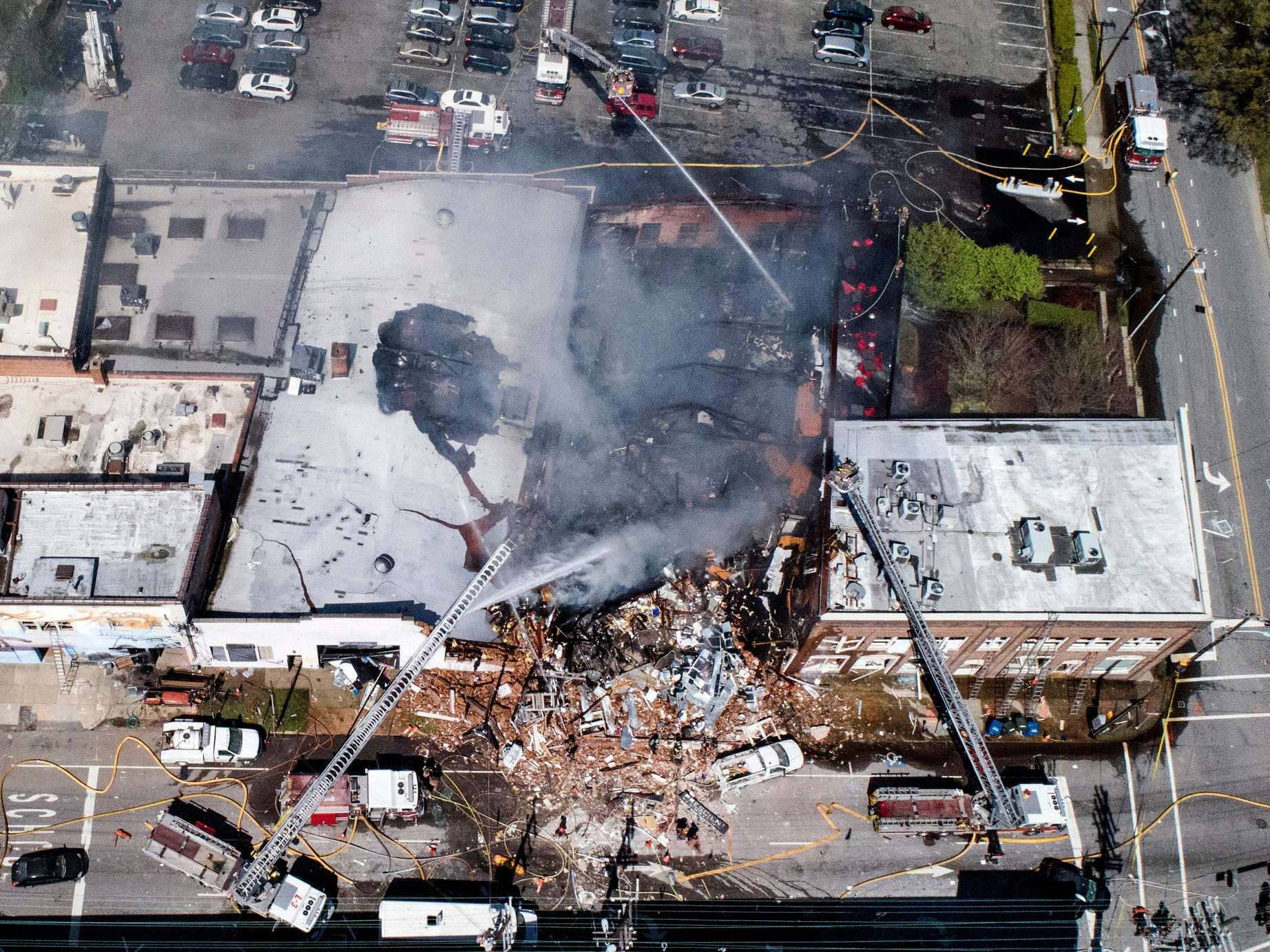 In this aerial photo, firefighters battle a fire at the scene of an explosion in Durham, N.C. Wednesday, April 10, 2019.
