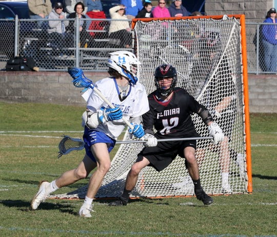 Dawson Felenchak of Horseheads looks for room behind the net as Noah Gold defends for Elmira in boys lacrosse April 9, 2019 at Horseheads High School.