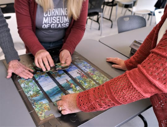 Corning Museum of Glass volunteers practice on a puzzle that museum visitors will be able to assemble during Spreak Break Week activities.