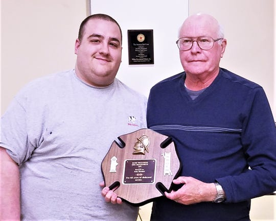 Bath Volunteer Fire Department Assistant Chief Mike Fiordo, left, presents a plaque to member John Burdick for 60 years of service.