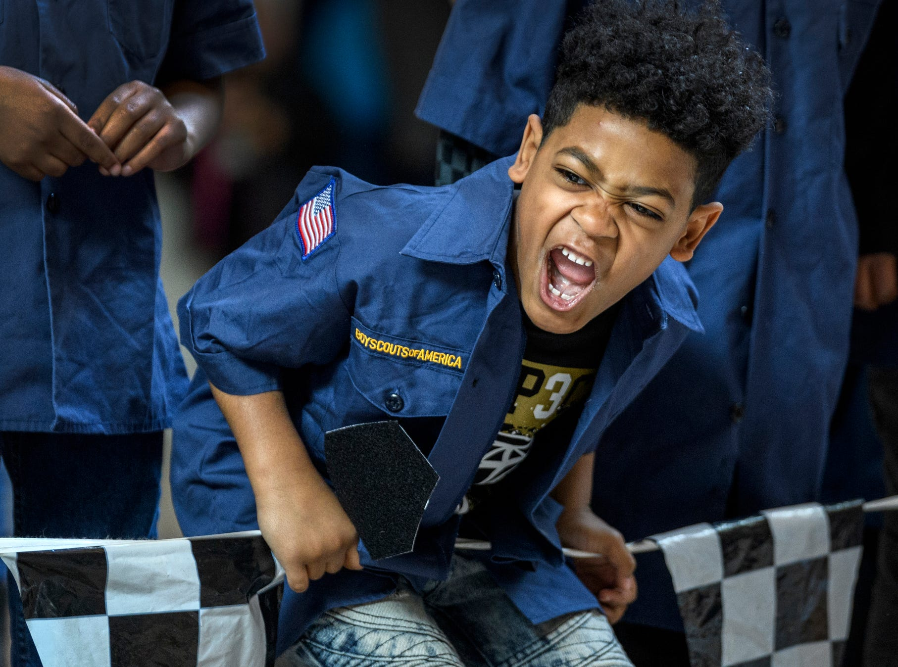 Jerry Hazelwood, a first-grader from Joshua Academy, cheers as he watches his pinewood derby car race down the track during the annual Scoutreach Pinewood Derby competition at Eastland Mall in Evansville, Ind., Saturday, March 16, 2019. Hazelwood won second place in the first-grade division.