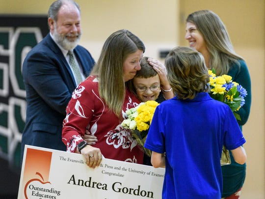 Special Education teacher Andrea Gordon embraces her children Karson, 11, center, and Aidan, 14, right, after being announced the 2019 High School Teacher of the Year during an assembly at North High School in Evansville, Ind., Wednesday, April 10, 2019.