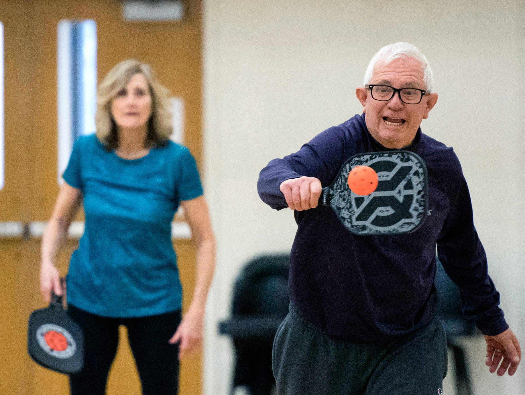 James Brown, front, returns the ball while playing a game of game of pickle ball with partner Jean Schmitt, back, at St. Peter's Methodist Church, Wednesday, March 20, 2019.