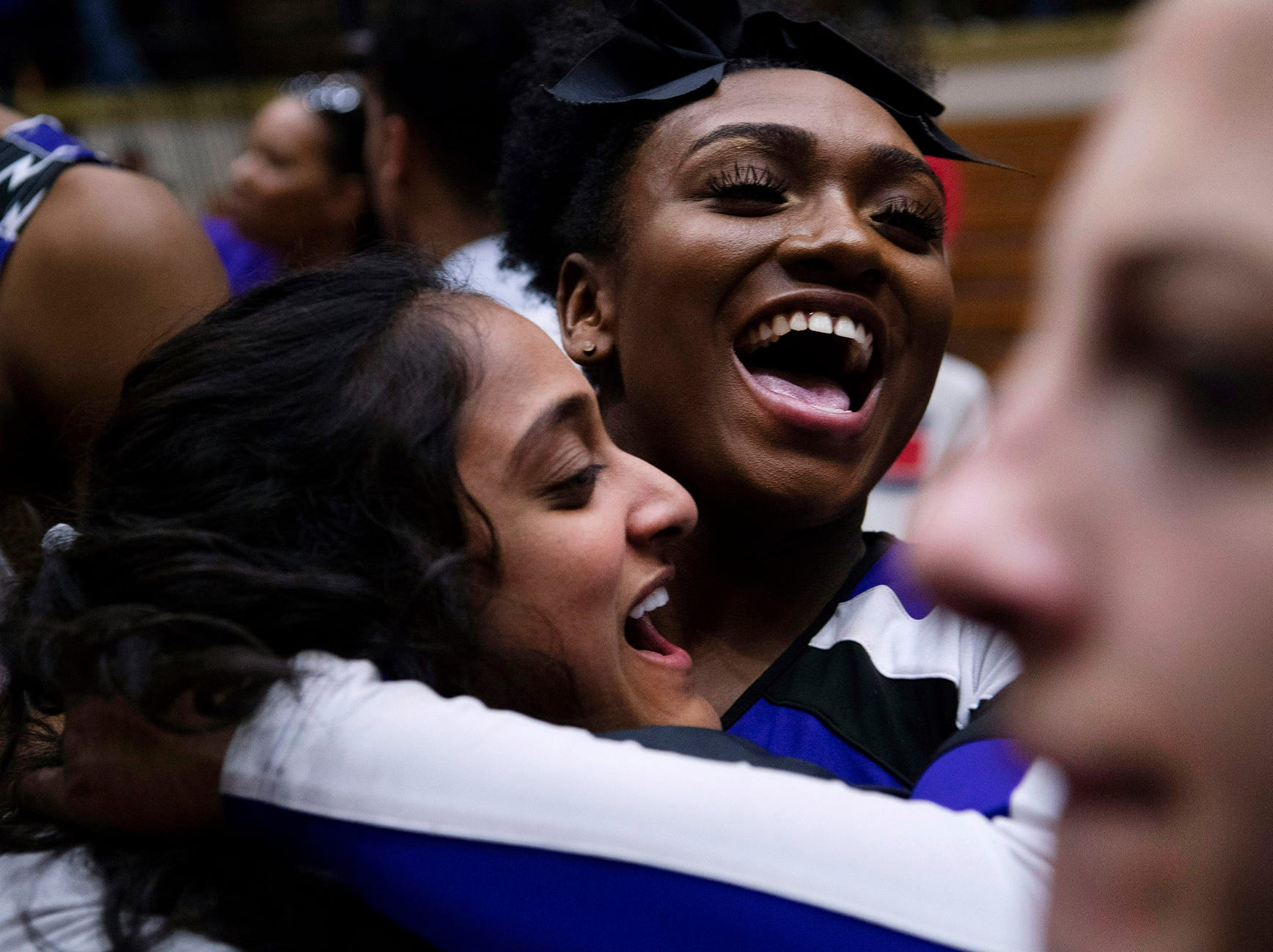 Ben Davis cheerleader Ashley Akin, top, celebrates with the students on the court after beating Center Grove in the 4A Boys Indiana Semi-State Basketball Tournament at the Hatchet House in Washington, Ind., Saturday afternoon, March 16, 2019. Ben Davis beat Central Grove to advance to next week's state championship.