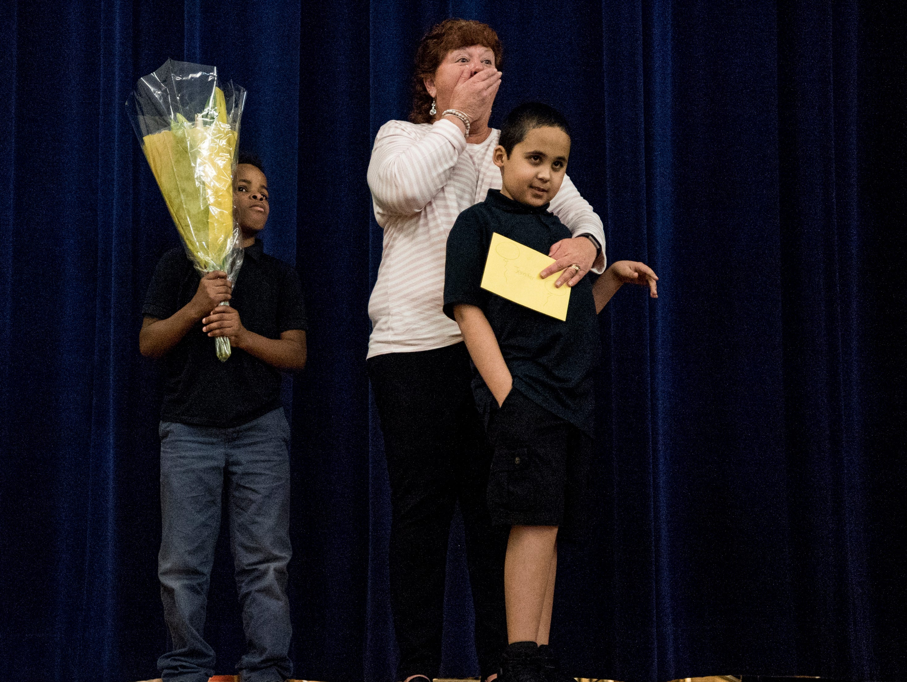 Jennifer L. Stoll, center, reacts to seeing several of her friends sitting in the front row of the auditorium as she is joined by two of her students Jakorvyan Heathers, left, and Darren Hooks, right, on stage during the awards assembly at Washington Middle School in Evansville, Ind., Wednesday, April 10, 2019. Stoll, who works in special education, was named the 2019 Middle School Teacher of the Year award.