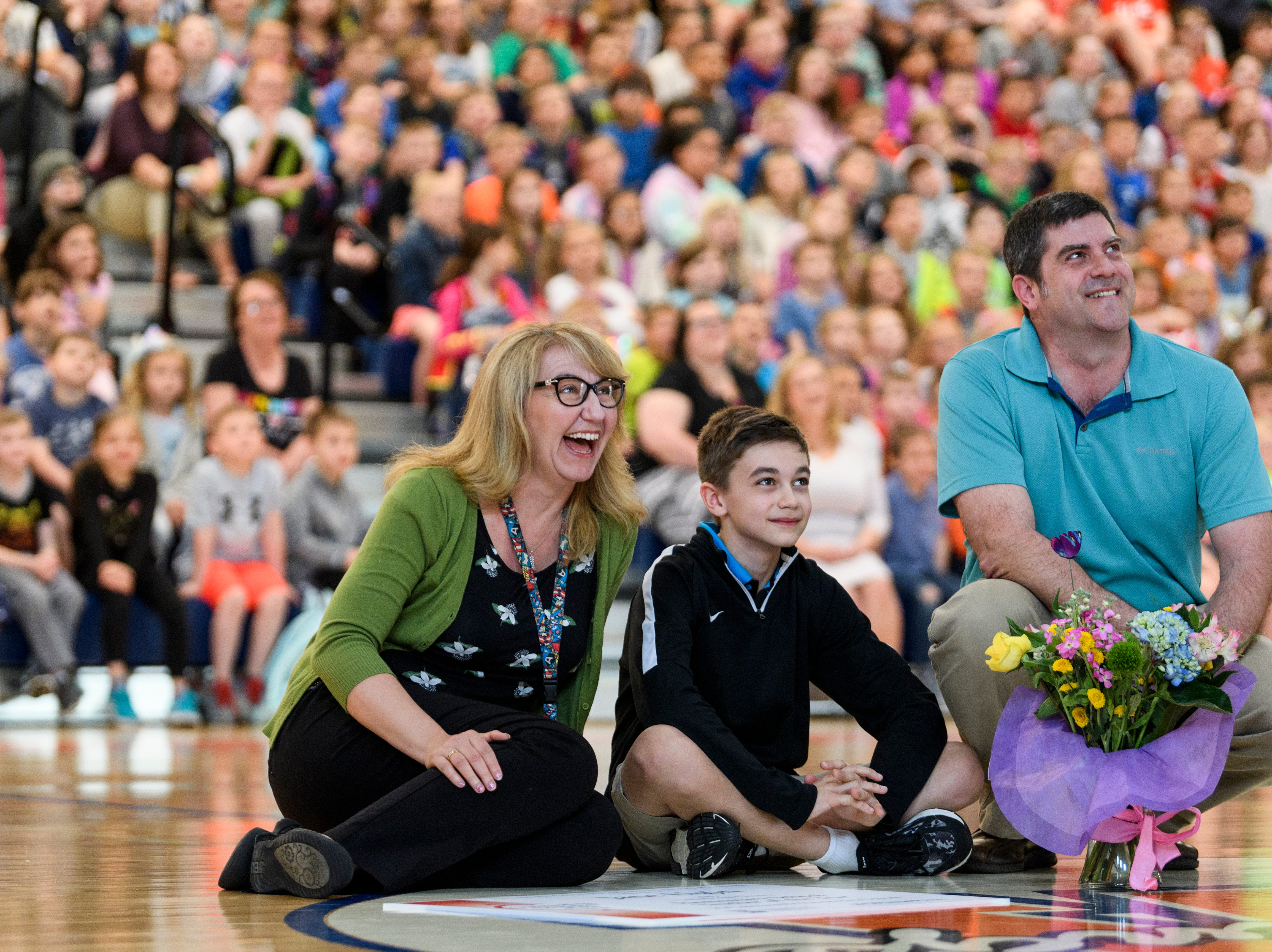 Jane Elgin, from left, laughs as she watches a video with her 13-year-old son Anthony, 13, and husband Brian Elgin during a school assembly held in her honor at McCutchanville School in Evansville, Ind., Wednesday, April 10, 2019. She was named Vanderburgh County's 2019 Elementary School Teacher of the Year.
