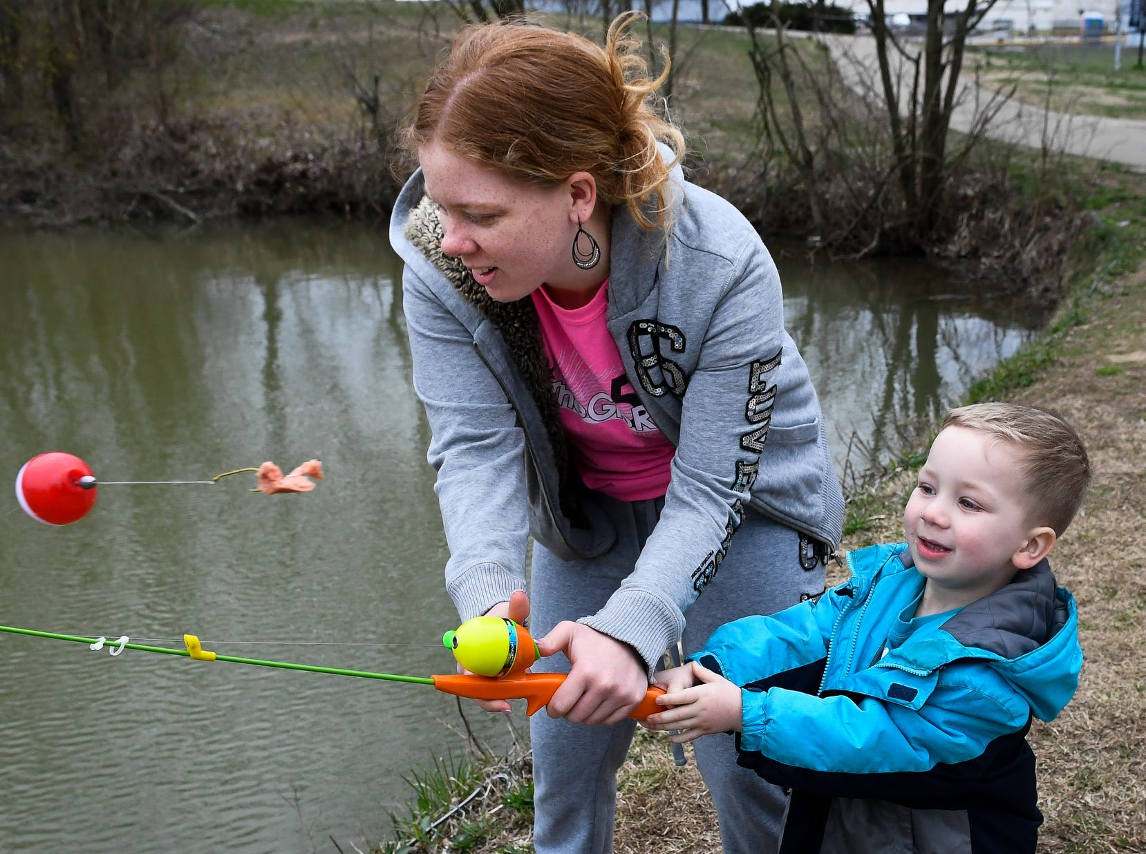 Mastering the art of the cast, Yesenia Deleon helps Kayden Kress, three years-old, launch his piece of hotdog out into the lake at Evansville's Garvin Park during a last day of spring break family fishing trip, Friday, March 29, 2019.