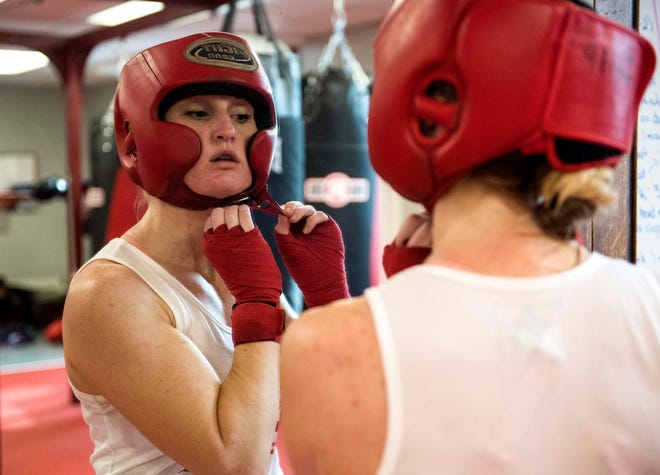 """Hoses fighter Paige """"MF"""" Jones, Posey County EMS, straps on headgear before sparing during the last practice before the 2019 Guns & Hoses event at Ford Center on Saturday, April 13, 2019. Jones will take on Evansville Police Departments Taylor Merriss for the main event."""