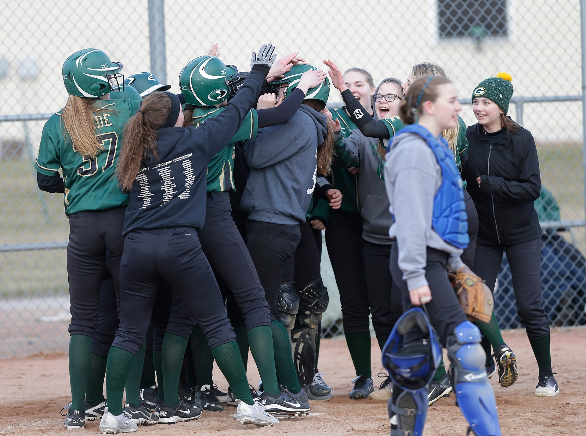 The Laconia High School softball congratulates Kennedy Krohn after her grand slam homerun against Winnebago Lutheran Academy April 9, 2019 during their game in Fond du Lac, Wis. Laconia won the game 25-9. Doug Raflik/USA TODAY NETWORK-Wisconsin
