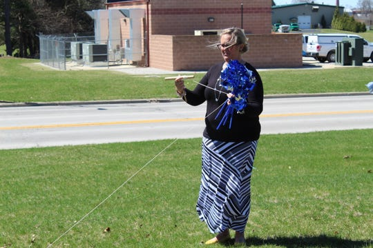 Dori Otteny, an account clerk with Sandusky County Department of Job and Family Services measures uses a string to measure for workers to plant pinwheels outside the department's building to raise awareness for child abuse.