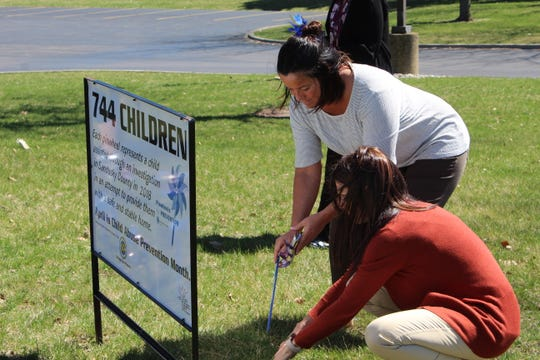Sandusky County Department of Job and Family Services Director Melanie Allen, far, and supervisor Kelly Beeker, near, place a pinwheel in the front lawn of the Sandusky County Complex to signify the number of children assisted by the county in 2018.