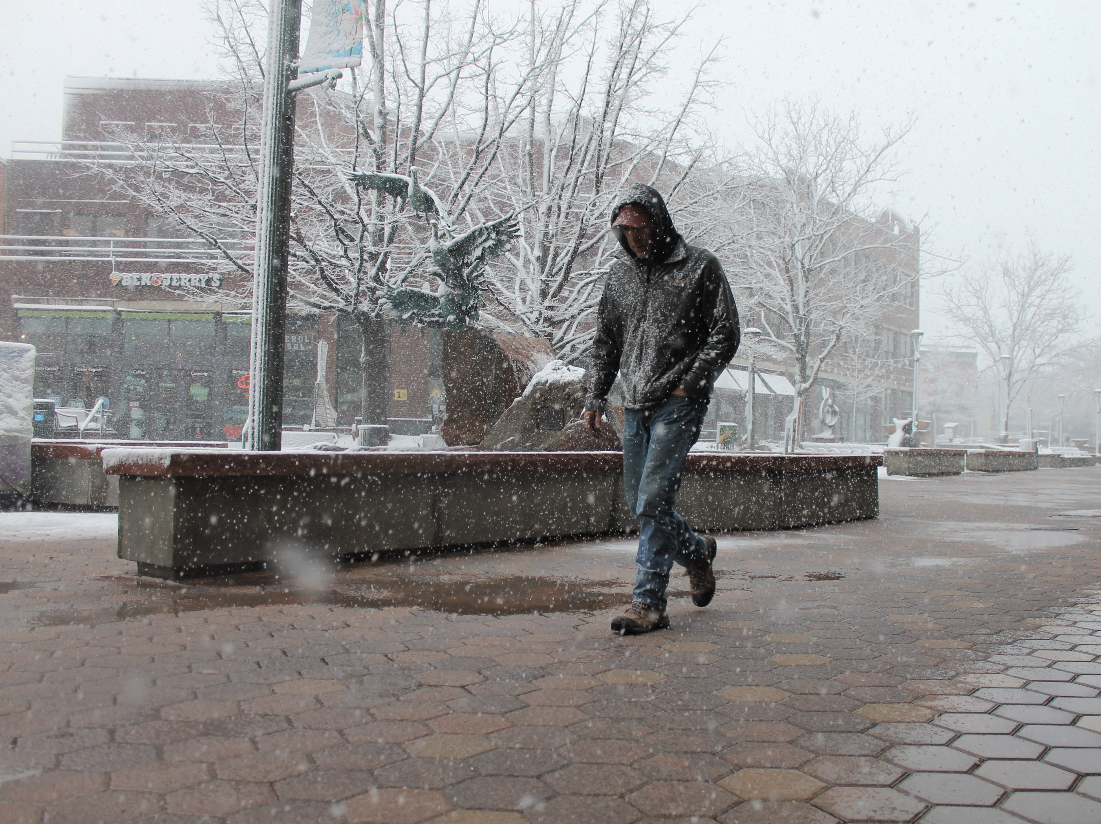 Nathan Emmons walks through Old Town square Wednesday, April 10, after a lunch break. Emmons is from Montana,  he said, and the Wednesday blizzard reminded him a bit of home.