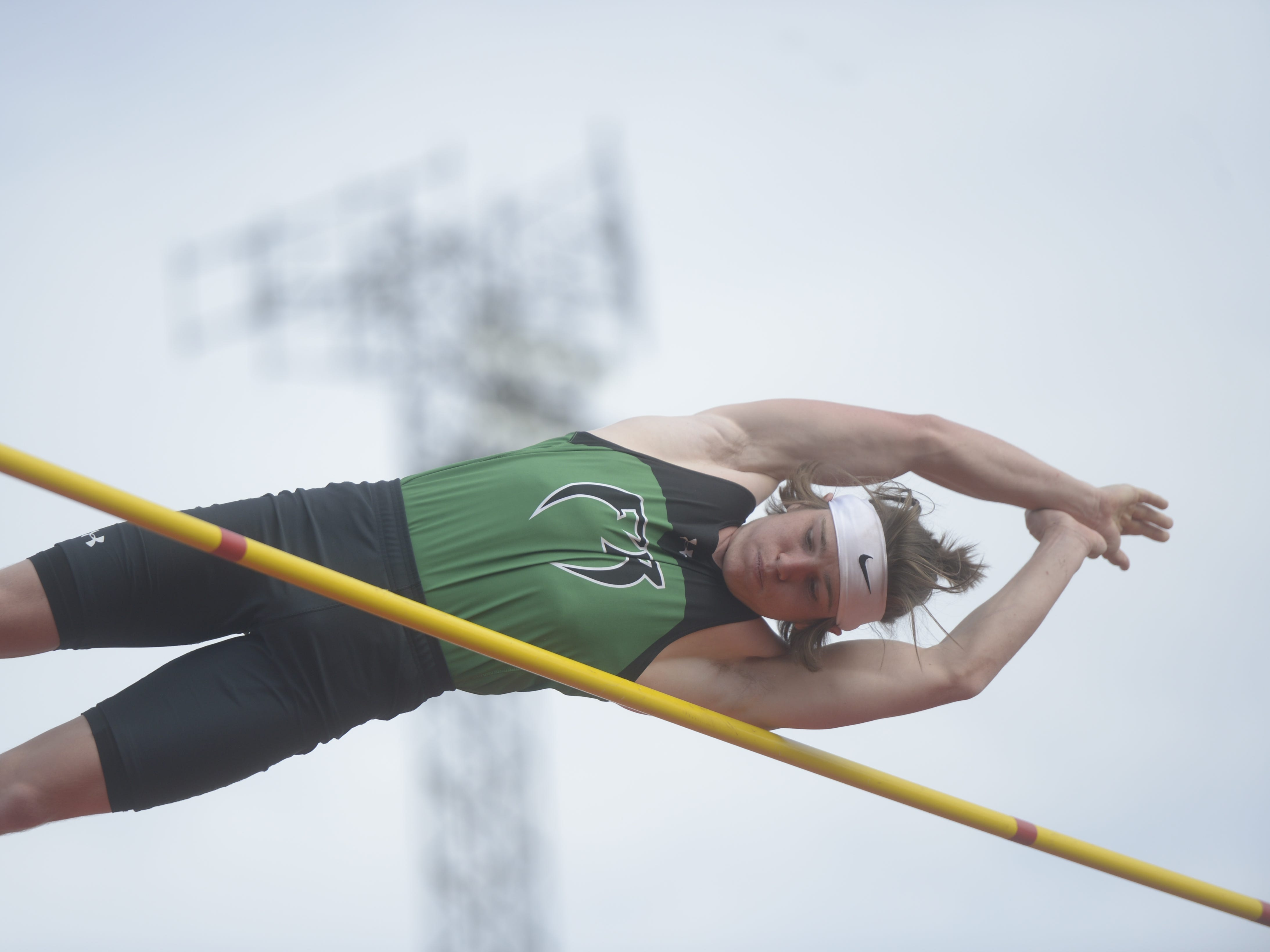 Fossil Ridge High School's Adam Curran clears the bar in the pole vault competition at the Fort Collins city meet at French Field on Tuesday, April 9, 2019.