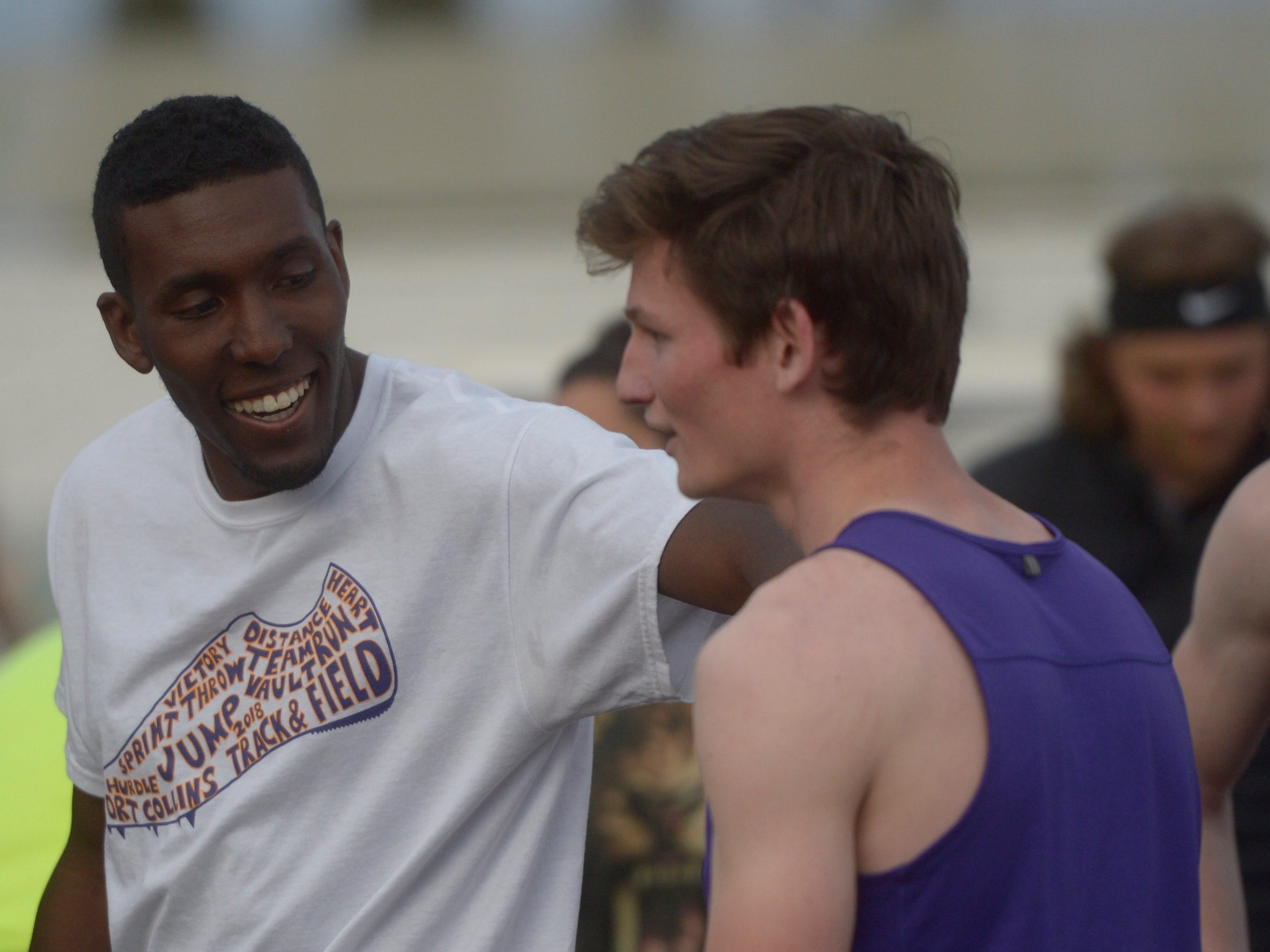 Fort Collins High School assistant coach Ray Bozmans congratulates Joey Maguire after the Lambkins won the 1,600 relay at the Fort Collins city meet at French Field on Tuesday, April 9, 2019.