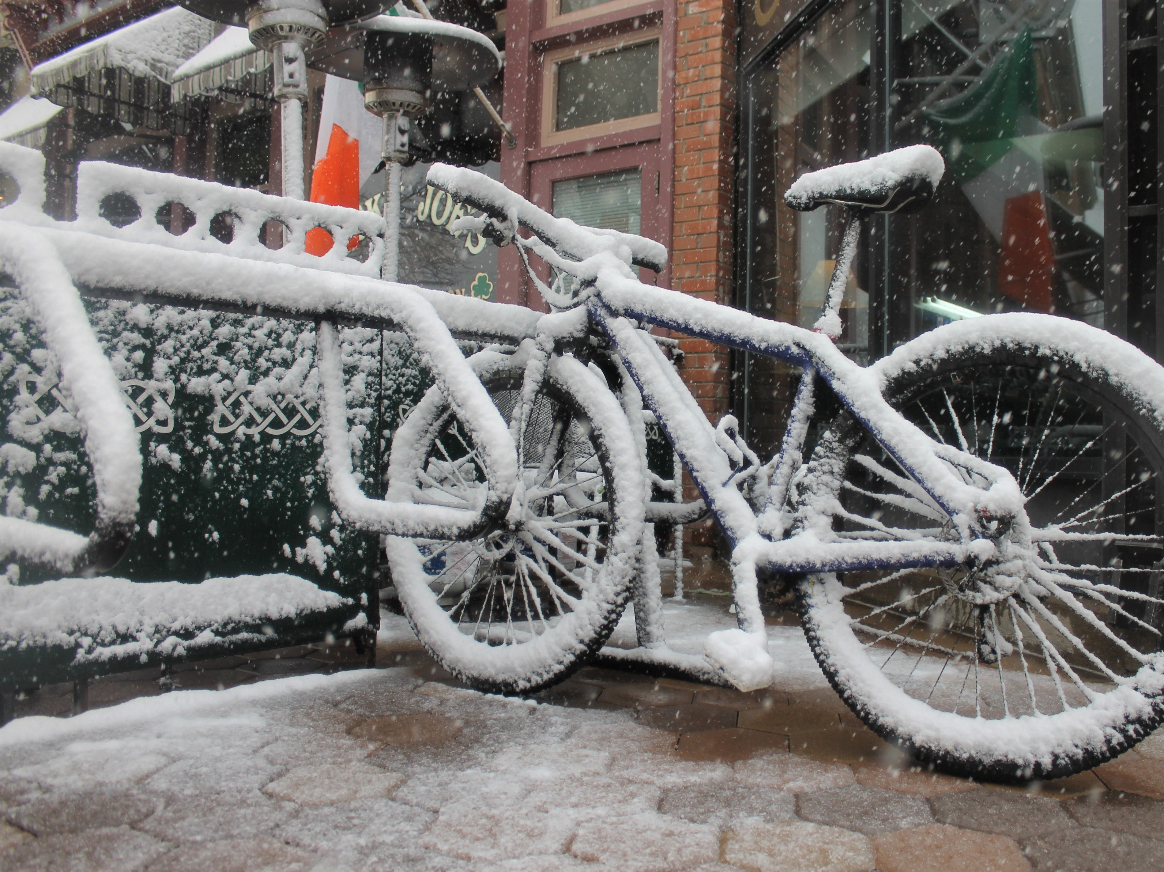A bike collects snow in Old Town as a blizzard roles in to Fort Collins Wednesday, April 10.
