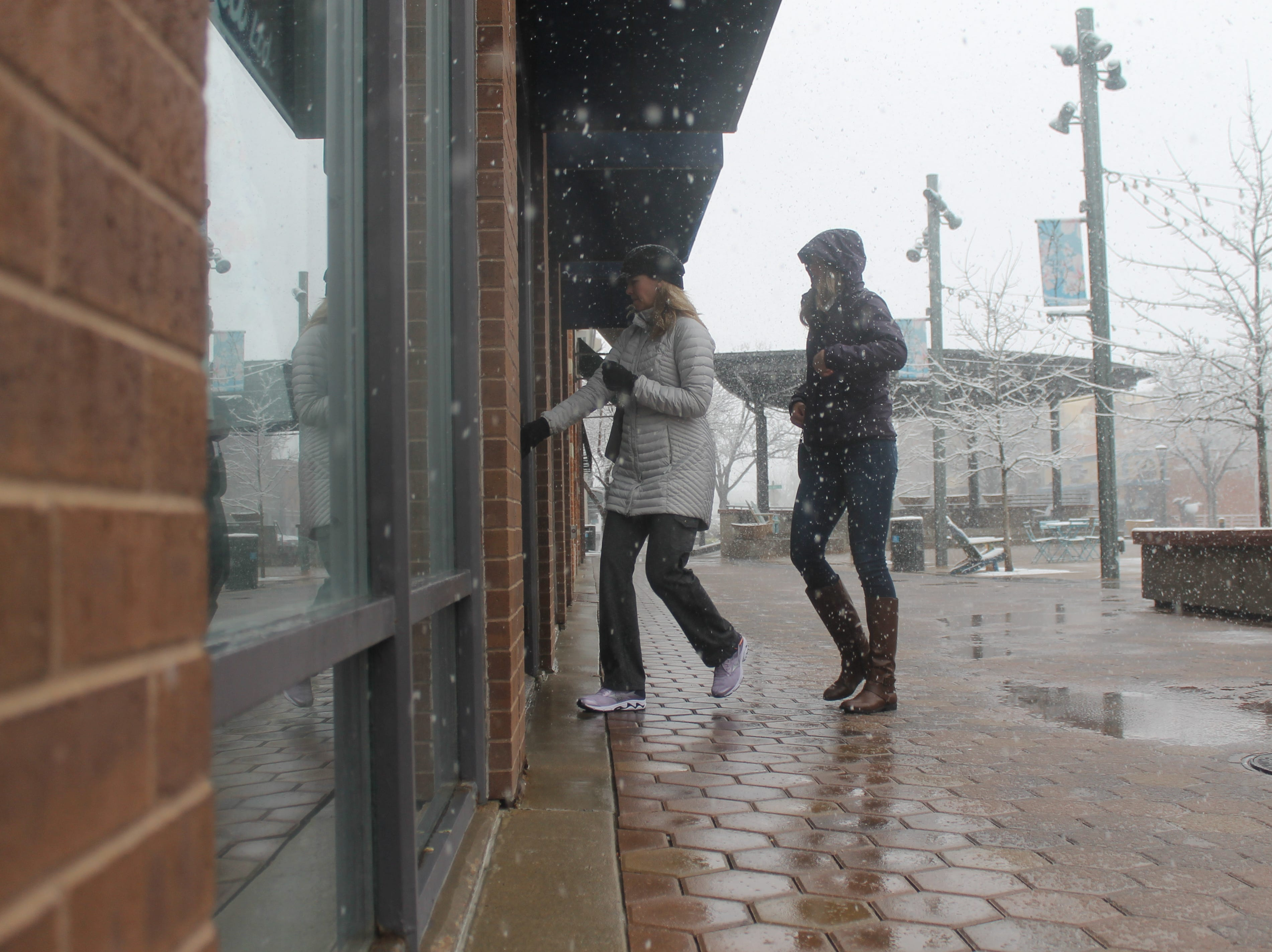 A mother and daughter brave a blizzard Wednesday, April 10, to go shopping in Old Town Fort Collins.