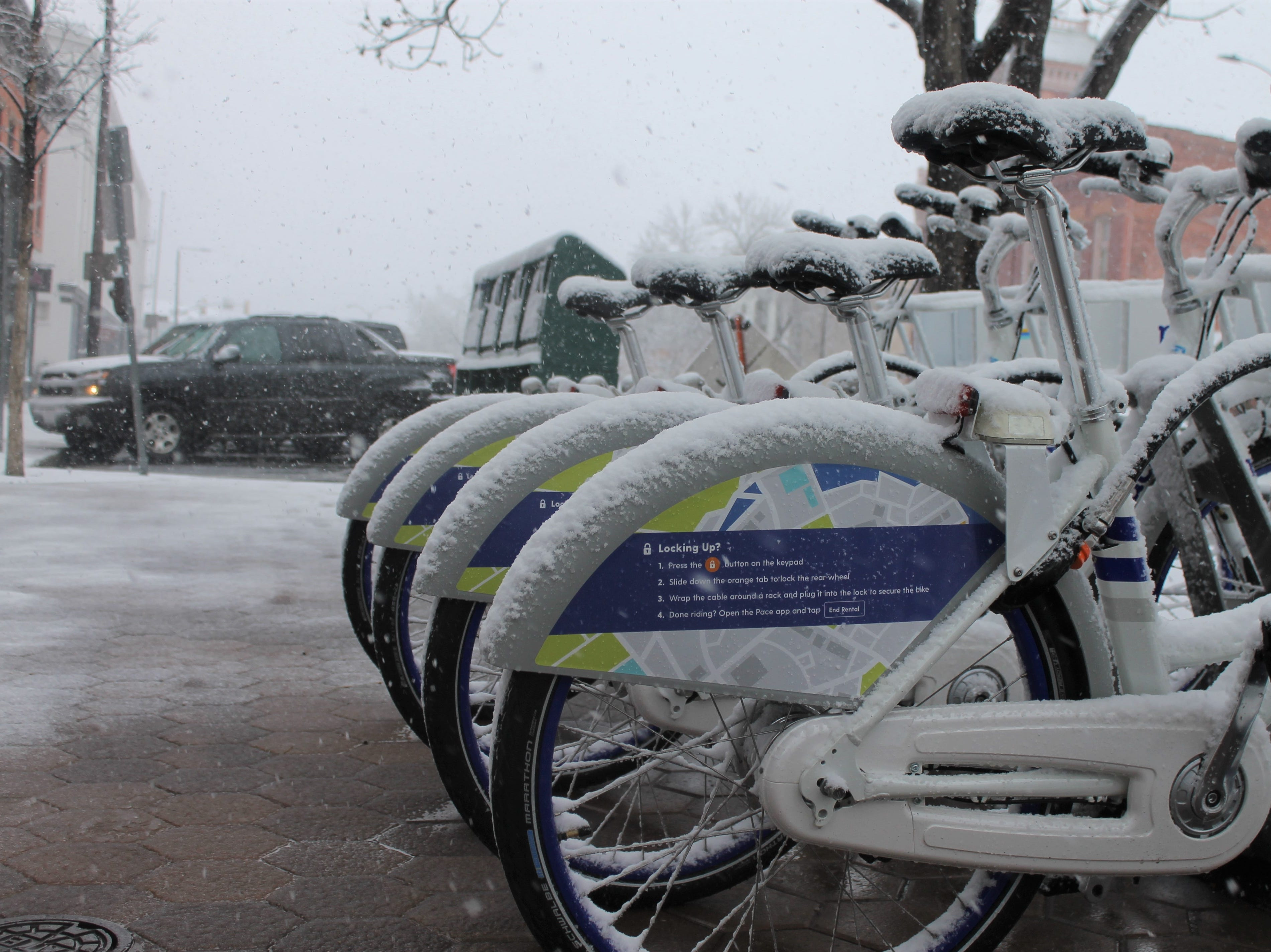 Bikes gather snow in Old Town Wednesday as a spring blizzard rolls into Fort Collins.