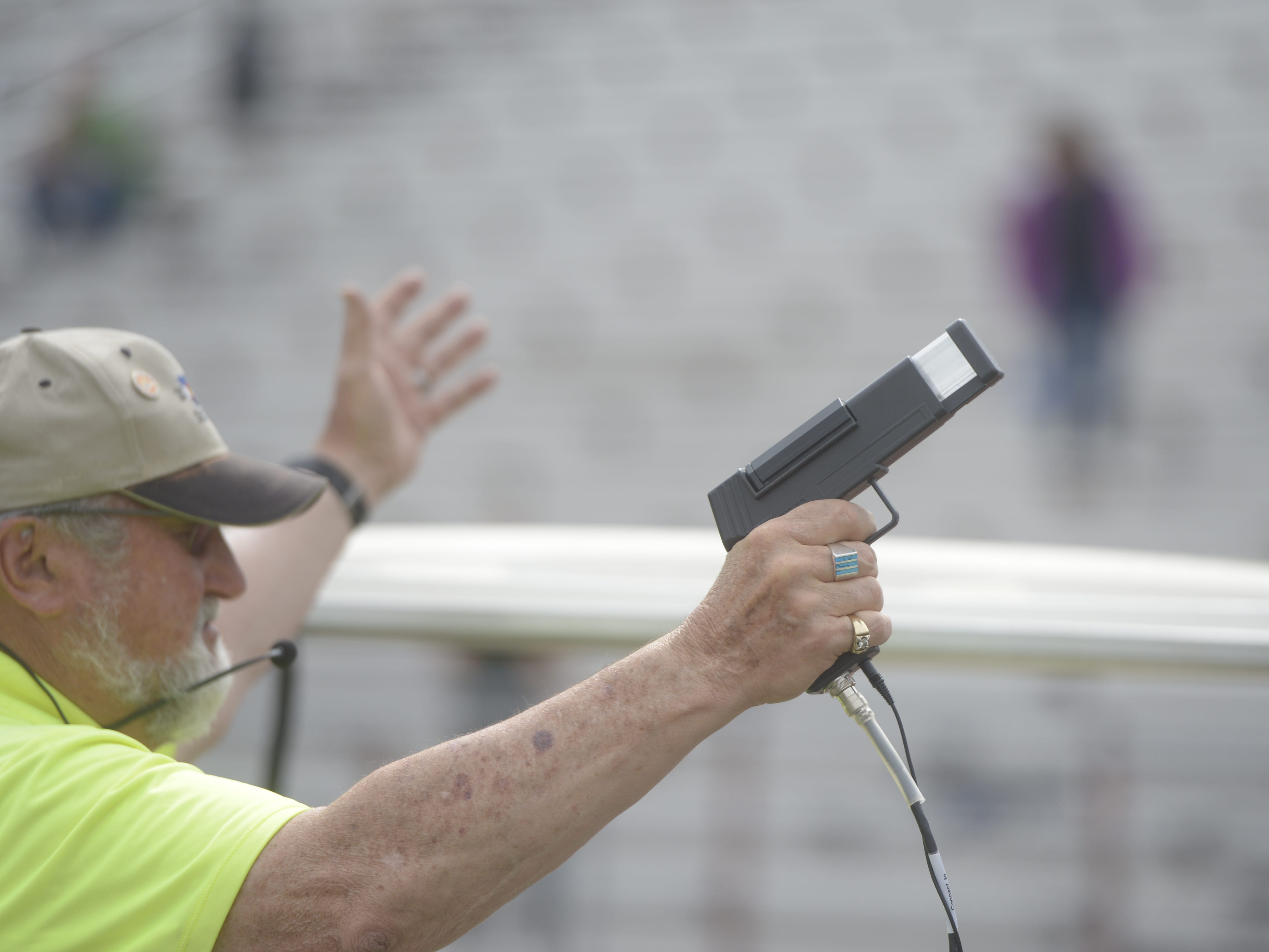 An official prepares to fire the starting gun at the Fort Collins city meet at French Field on Tuesday, April 9, 2019.