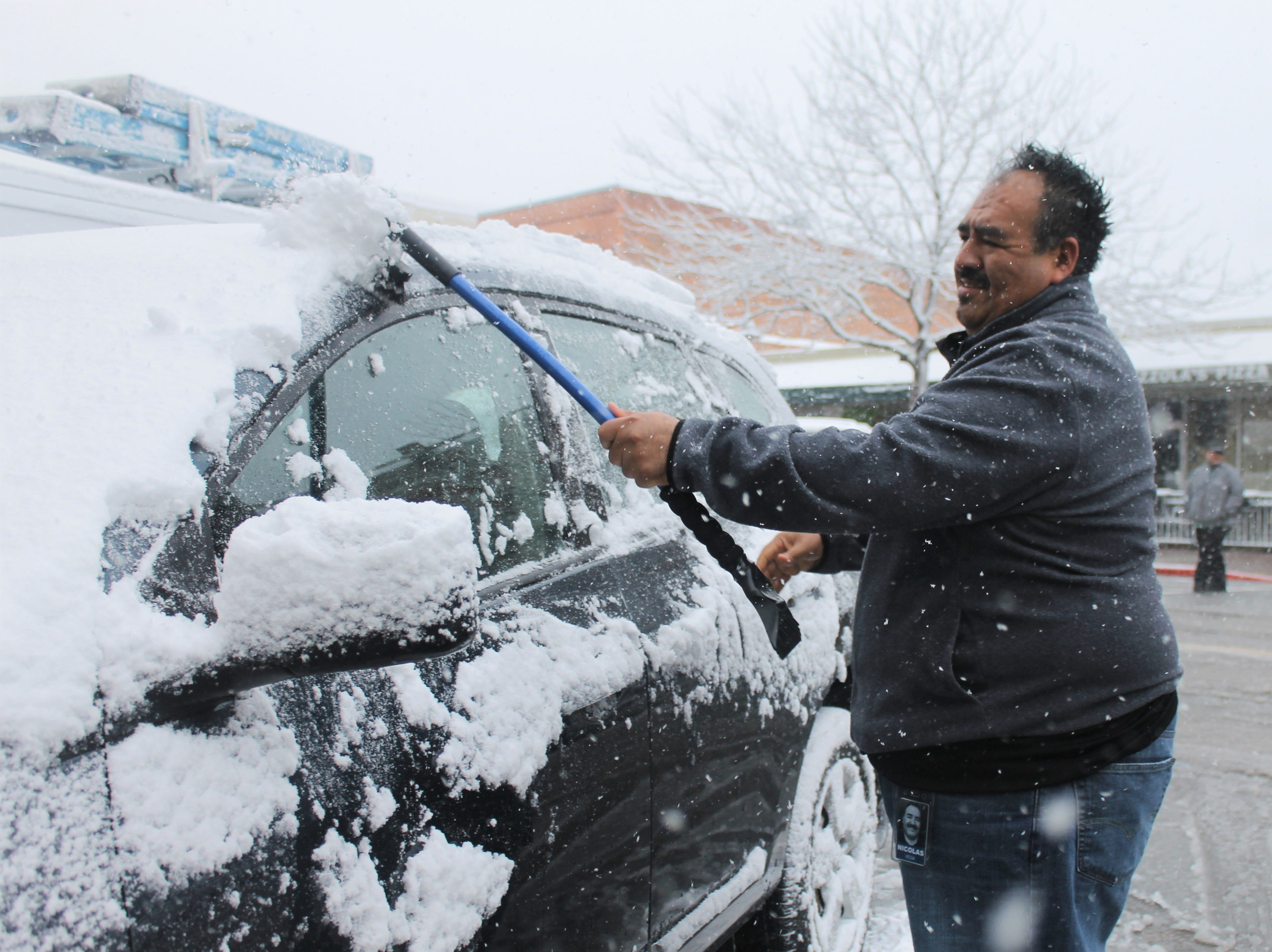 Alex Varga clears snow off his car in Old Town Wednesday as a blizzard rolls in.