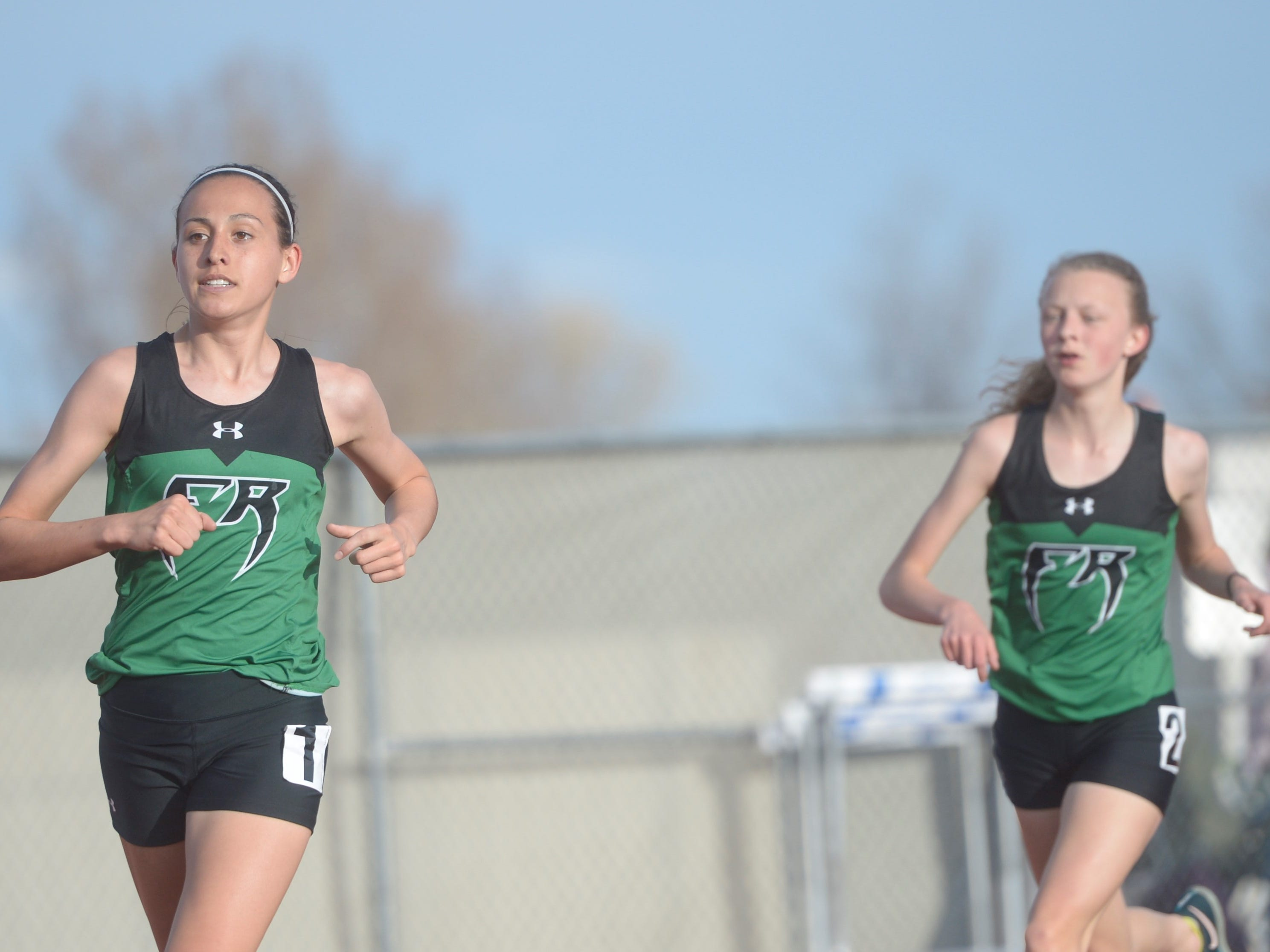 Fossil Ridge High School's Isabelle Missimer, left, and Caitlin Hunt compete in the 3,200 run at the Fort Collins city meet at French Field on Tuesday, April 9, 2019.