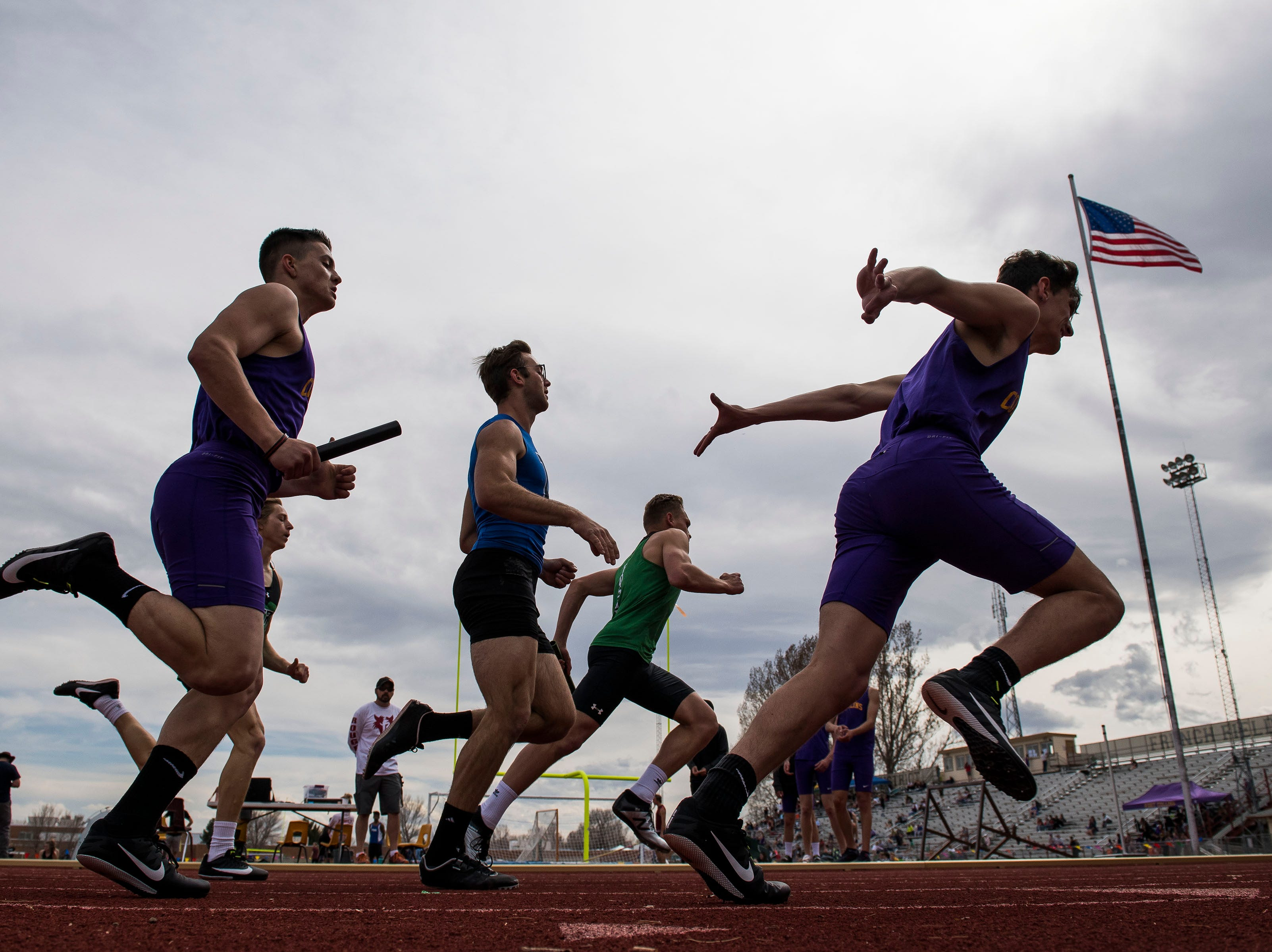 Fort Collins High School's Caleb Reed looks to hand off to teammate Ian Petruska in the boys 4x200-meter relay during the Randy Yaussi City Track Championships on Tuesday, April 9, 2019, at French Field in Fort Collins, Colo.