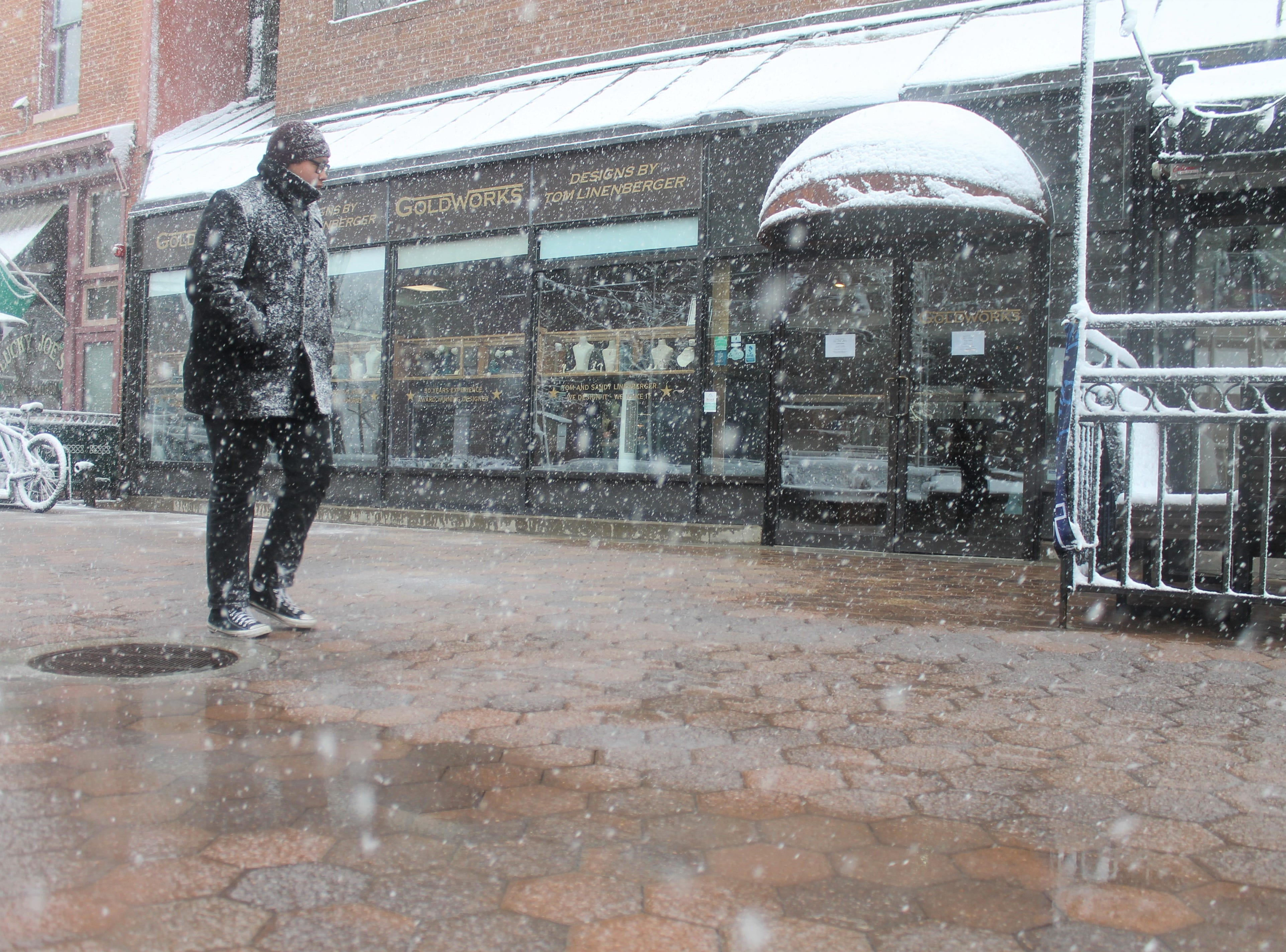 Teak Rouillard takes a stroll in the snow Wednesday, April 10, in Old Town. With about 30 minutes left of his lunch break, he decided to get out and enjoy the snow.