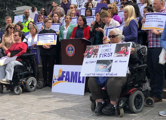 Colorado Democratic Sens. Angela Williams and Faith Winter listen behind the podium as activist Judith Marquez speaks in favor of their paid family leave bill at a rally outside the statehouse on Tuesday, April 9, 2019, in Denver. (AP Photo/Jim Anderson)
