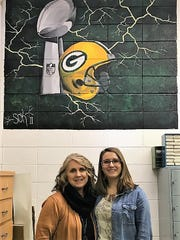 Lena art teacher Vicki Magee, left, and S.T.E.F board member Tara Seefeldt are seen below a painting completed by Stefanie Kanack while she was a student at Lena High School. The Lena art department received $500 from S.T.E.F., which also gave $3,000 to the high school scholarship fund.
