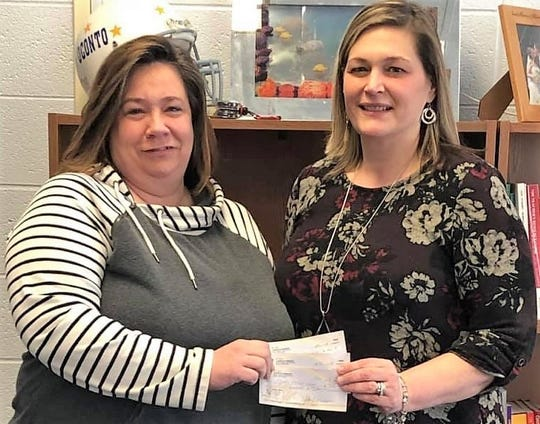 S.T.E.F. vice president Gail Madson hands a $500 check to Oconto School District superintendent Emily Miller, which will go to a hydroponic garden at the middle school.