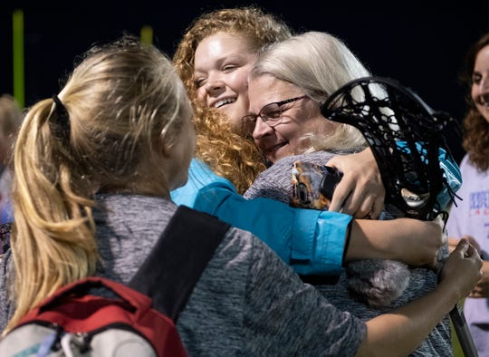 Members of the Riverside girls lacrosse team hug form coach DeAnn Louis after the game against Spartanburg at Riverside High School Tuesday, April 9, 2019.