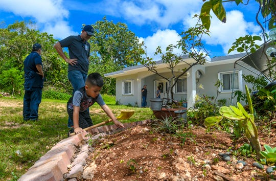 Four-year-old Zyan Mendiola plays with sleeping grass growing in a small garden in front of his parents Bryan and Brittany Mendiola's home in Yigo, during a compliance inspection visit by CHamoru Land Trust Commission Administrative Director Jack Hattig III, center, and Department of Land Management Land Agent Glenn Eay, left, on Wednesday, April 10, 2019. Brittany Mendiola says the family had to secured a mortgage to build their three-bedroom/two-bathroom home and so far invested approximately $35,000 into the property. The family was then informed by the commission that their lease was to be voided.
