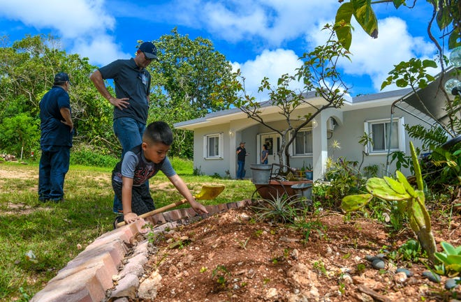 Zyan Mendiola, 4, plays with sleeping grass in a small garden during a compliance inspection visit by CHamoru Land Trust Commission Administrative Director Jack Hattig III, center, and Department of Land Management Land Agent Glenn Eay, left, in this April 10 file photo.