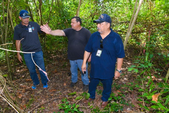 Lease holder David Janz, center, explains his problem of access to a lot granted to by the Chamorro Land Trust Commission after showing CLTC Administrative Director Jack Hattig III, left, and Department of Land Management Land Agent Glenn Eay a property marker during a compliance inspection in Dededo on Wednesday, April 10, 2019. Janz, who has a lease for Land Trust property indicated that abandoned vehicles and discarded items on an adjoining lot restricts access to the lot he was granted for residential use under the land program.