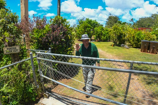 Agricultural lease holder Robert Celestial secures a gate providing security to a two-acre lot granted to him for use by the CHamoru Land Trust Commission after a compliance inspection visit in this April 10 file photo.
