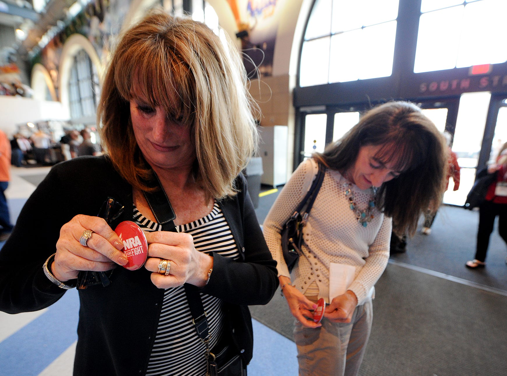 Susan Bryant, left, of New Palestine, and Cathy Arnold, of Greenfield, put on buttons at the NRA Stand and Fight Rally during the 143rd National Rifle Association Annual Meeting at Lucas Oil Stadium, Saturday, April 26, 2014, in Indianapolis.