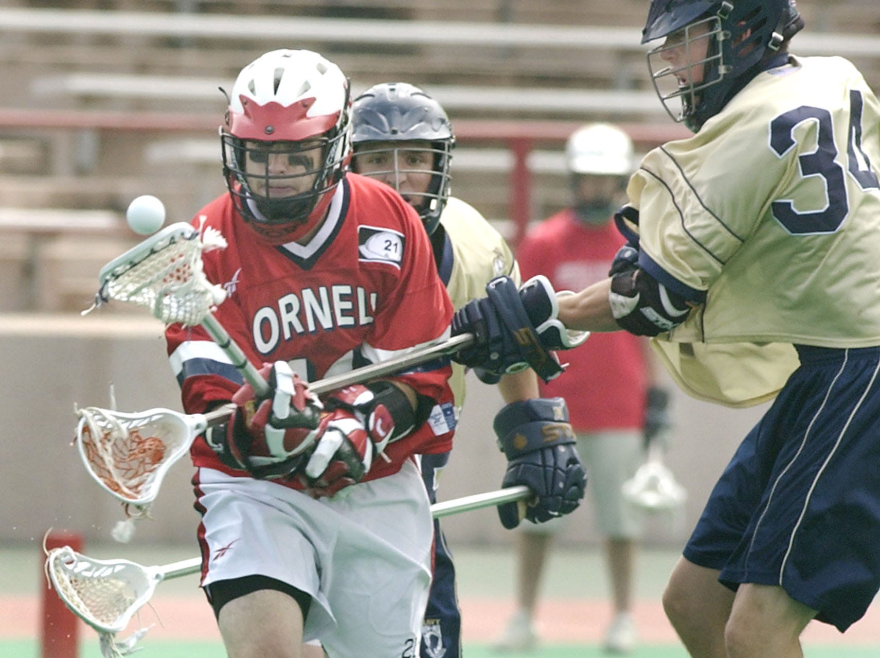 Cornell's Ian Rosenberger, left, has the ball knocked loose by Navy's Mitch Hendler (34) during the second quarter of their NCAA Division I lacrosse quarterfinal game in Ithaca, N.Y. Sunday, May 23, 2004. Navy won 6-5.