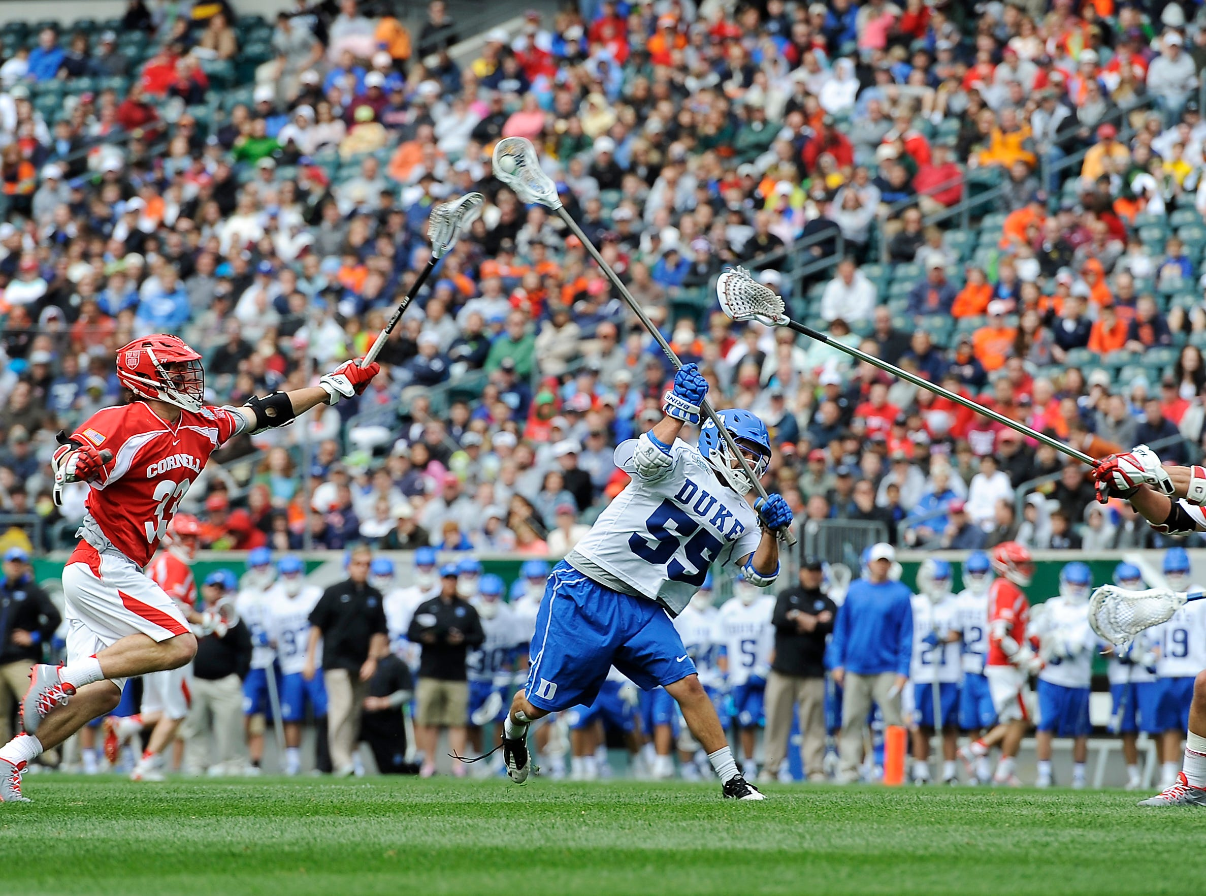 Duke's Bill Conners (55) takes a shots on goal and score while Cornell's Connor Buczek (33) defends during the first half of an NCAA division 1 semifinal lacrosse game on Saturday, May 25, 2013, in Philadelphia.