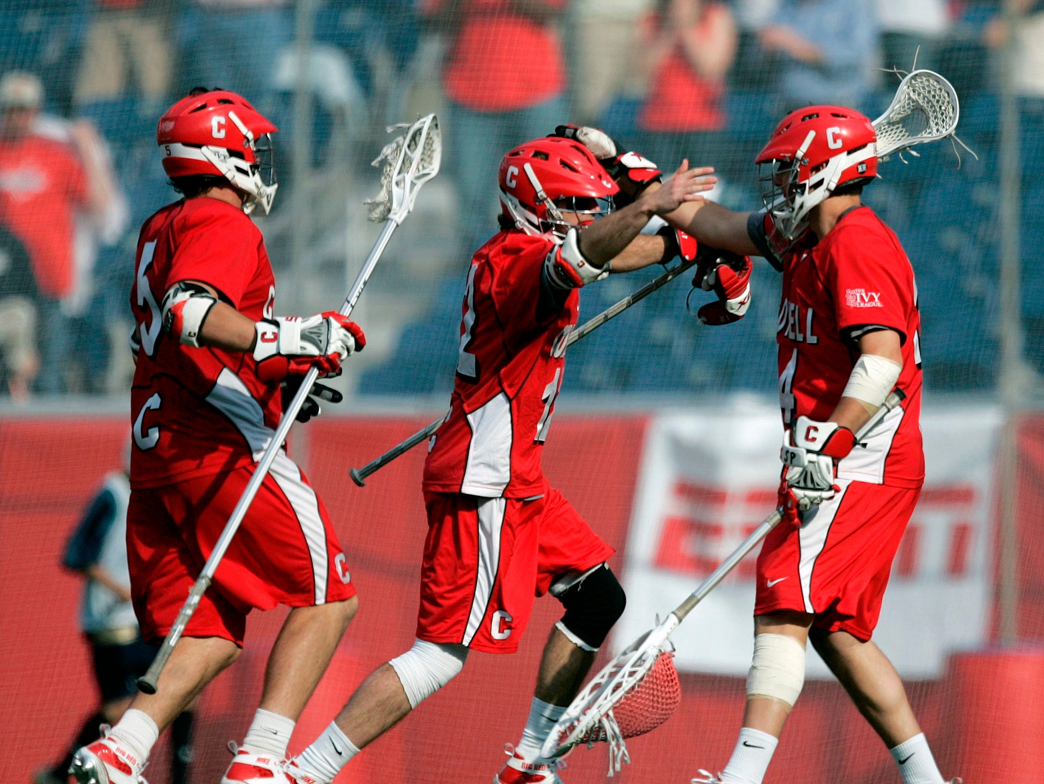 Cornell's Matt Moyer, center, and Pierce Derkac, left, celebrate with goalie Jake Myers after Cornell beat Virginia 15-6 in an NCAA Division 1 Men's lacrosse  semifinal game in Foxborough, Mass., Saturday, May 23, 2009.