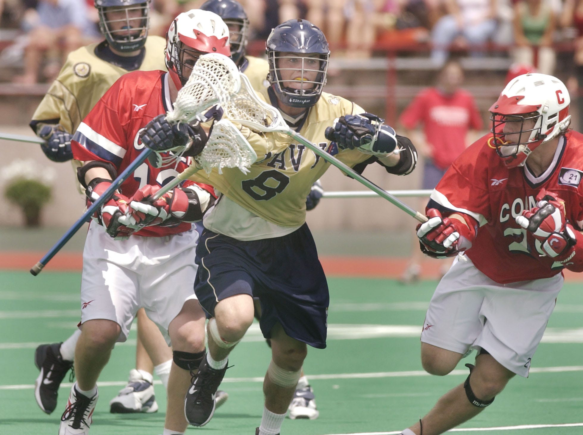 Navy's Steve Looney (8) runs between Cornell's Cameron Marchant, right, and Kevin Nee during the fourth quarter of their NCAA Division I lacrosse quarterfinal game in Ithaca, N.Y. Sunday, May 23, 2004. Navy won 6-5.