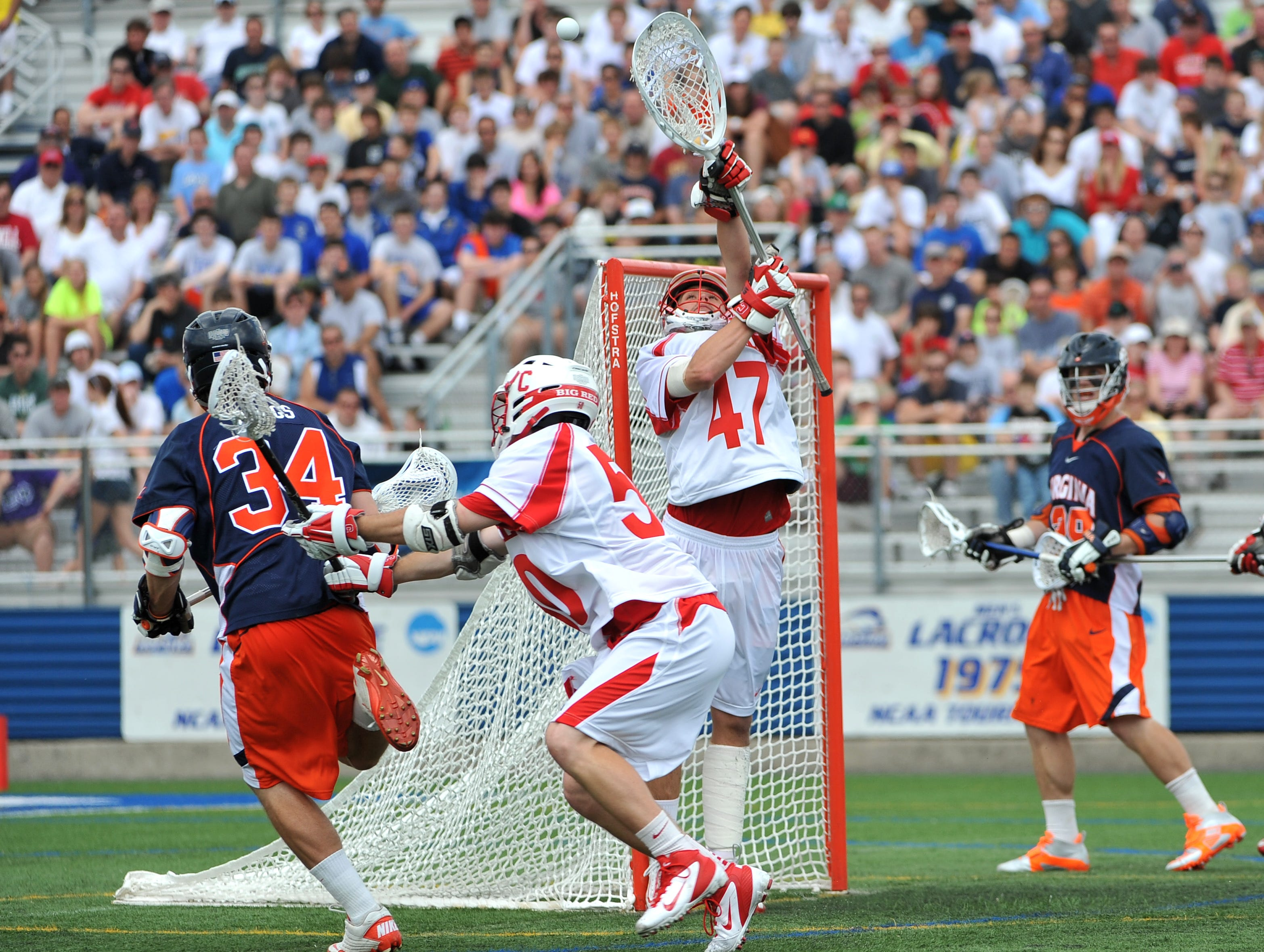 Cornell goalie AJ Fiore blocks a shot on goal by Virginia's Colin Briggs (34) as Cornell's Shane O'Neill (50) defends during the third quarter of an NCAA men's Division I lacrosse tournament quarterfinal on Saturday, May 21, 2011, at Hofstra University in Hempstead, N.Y.