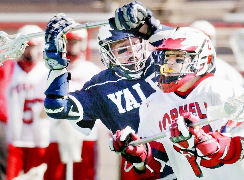 2004: Cornell junior Justin Redd looks for an open pass while battling Yale's Dennis Barry during the first half of Sunday's game at Schoellkopf Field, Cornell won 10-6 in its first game since George Boiardi died in a game March 17.