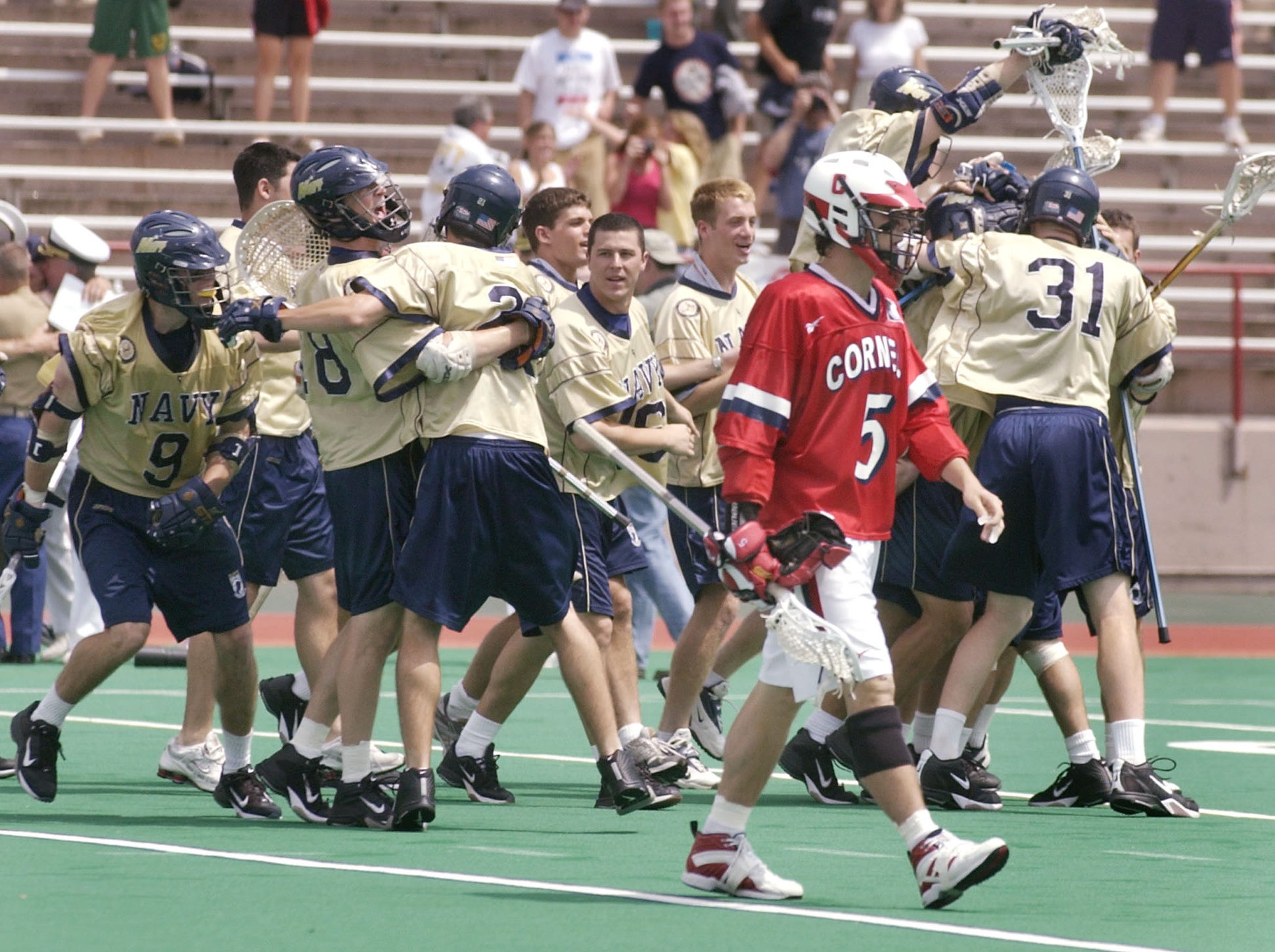 Navy players celebrate their 6-5 win in the quarterfinals of the NCAA Division I lacrosse championships as Cornell's Scott Raasch (5) walks off the field in Ithaca, N.Y., Sunday, May 23, 2004.