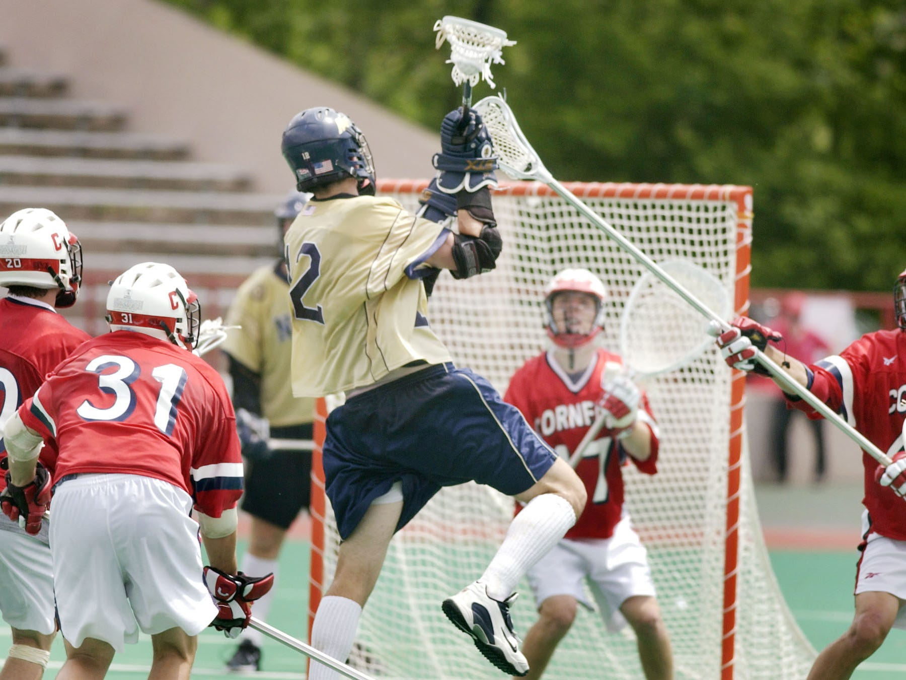 Navy's Graham Gill, center, shoots on Cornell goalie Matt McMonagle during the fourth quarter of an NCAA Division I lacrosse quarterfinal game in Ithaca, N.Y., Sunday, May 23, 2004. Navy won 6-5.