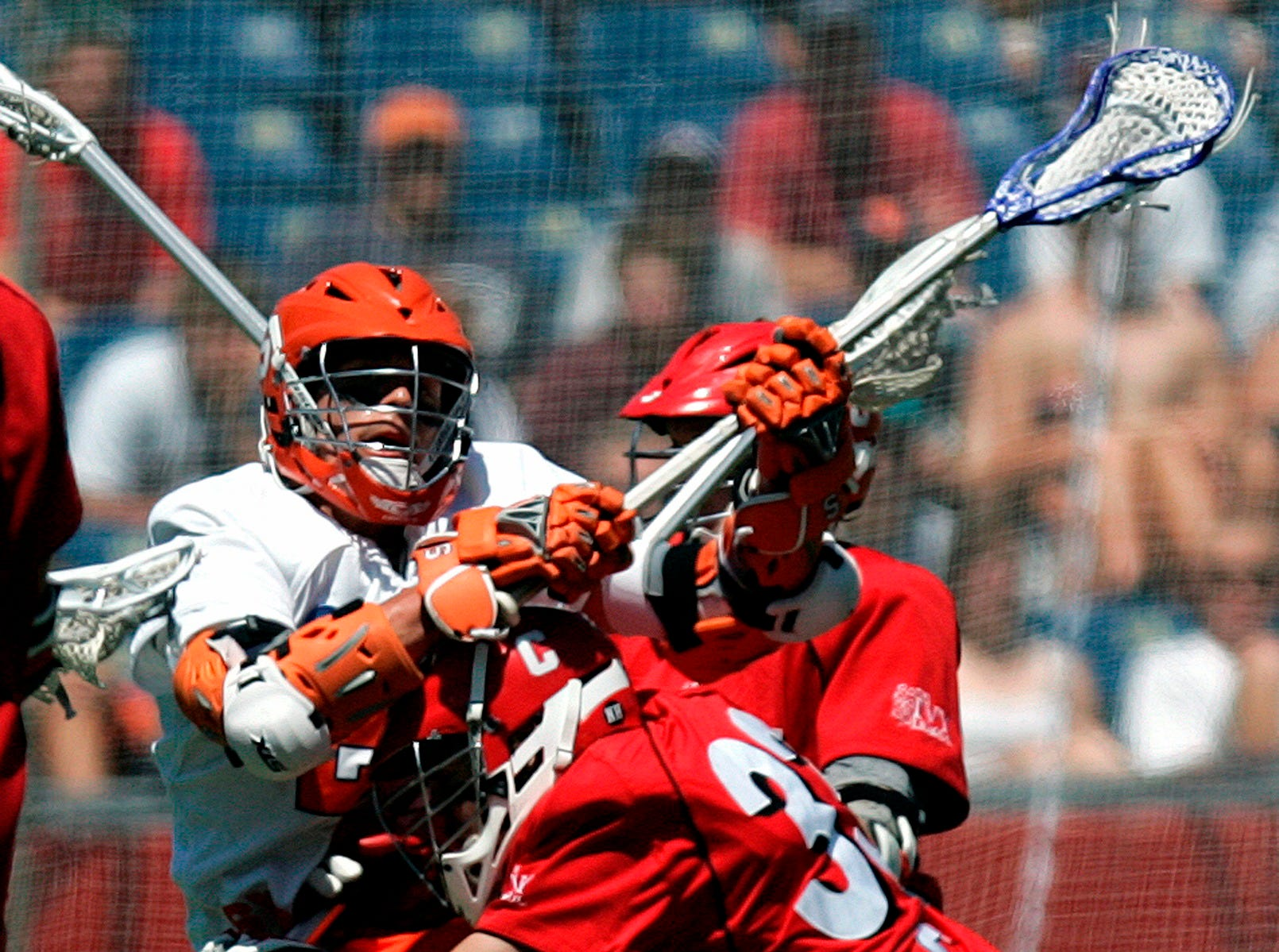 Cornell's Max Feely, center, checks Syracuse's Tim Desko, left, in the second quarter of an NCAA Division 1 Men's lacrosse championship game in Foxborough, Mass., Monday, May 25, 2009.